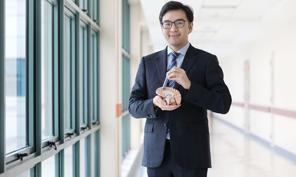 with a BrainPath obturator (blue) inside a sheath (transparent) and a model of the brain. It took him a year of trying before he succeeded in bringing the method to Singapore. ST PHOTO GAVIN FOO