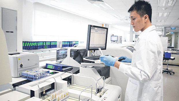 verifying a glucose test result at the Clinical Biochemistry Laboratory under Singapore General Hospital's Department of Clinical Pathology. PHOTO GIN TAY FOR THE STRAITS TIMES